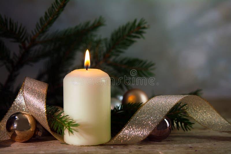 Vela ardiente blanca con la decoración de la Navidad o del Año Nuevo, spru imagen de archivo