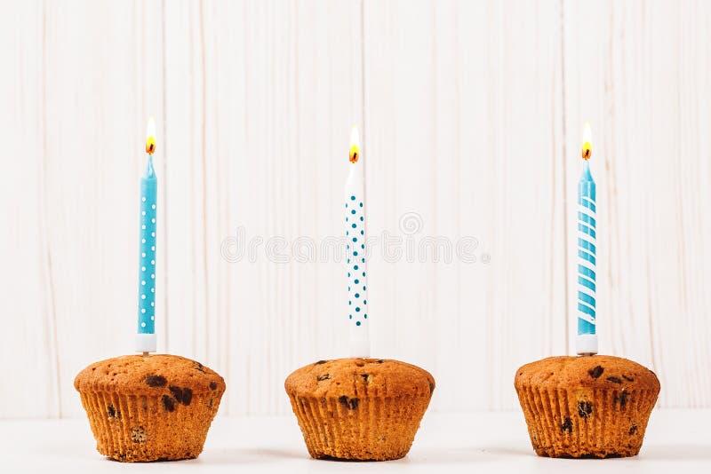 Vela ardiente del cumpleaños en la magdalena en un fondo de tablones de madera imagenes de archivo