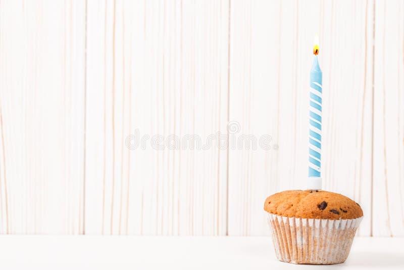 Vela ardiente del cumpleaños en la magdalena en un fondo de tablones de madera imágenes de archivo libres de regalías