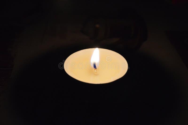 Vela ardiente hermosa en un fondo negro en la tabla fotos de archivo