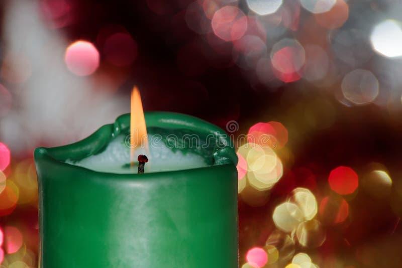 Vela ardiente verde contra luces de la celebración fotografía de archivo libre de regalías