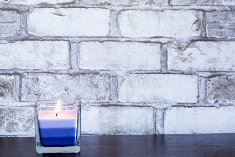 Vela ardiente violeta de la lavanda en los vagos de cristal y blancos de la pared de ladrillo fotos de archivo