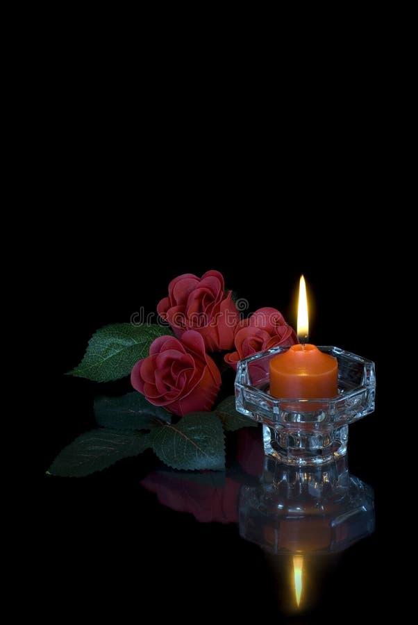 Vela ardiente y tres rosas rojas en un fondo negro imágenes de archivo libres de regalías
