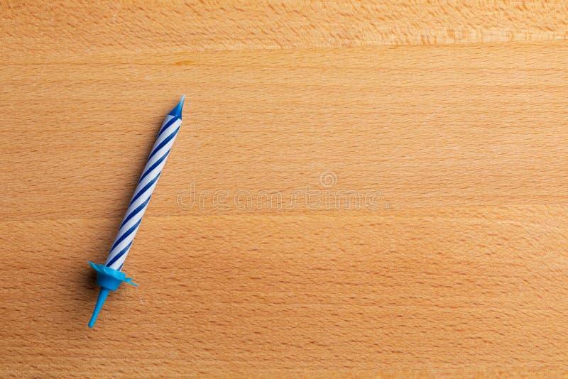 1 vela azul del cumpleaños en fondo de madera Para la tarjeta de felicitación del cumpleaños Espacio para insertar el texto foto de archivo