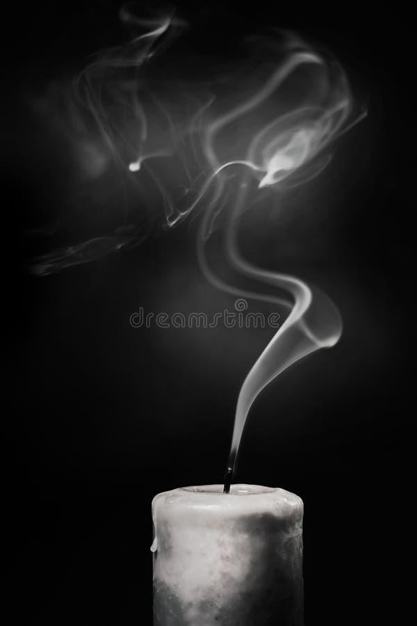 Vela blanca extinta con humo en un fondo negro fotos de archivo