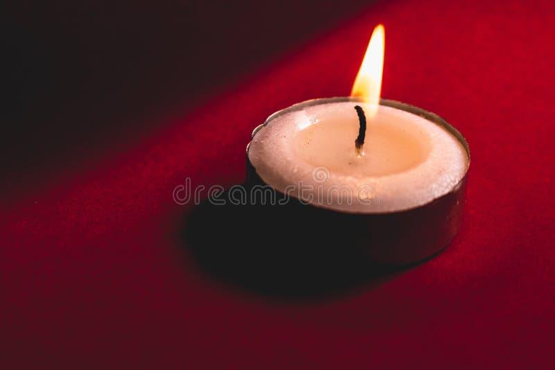 Vela blanca quemada en un fondo rojo imagenes de archivo