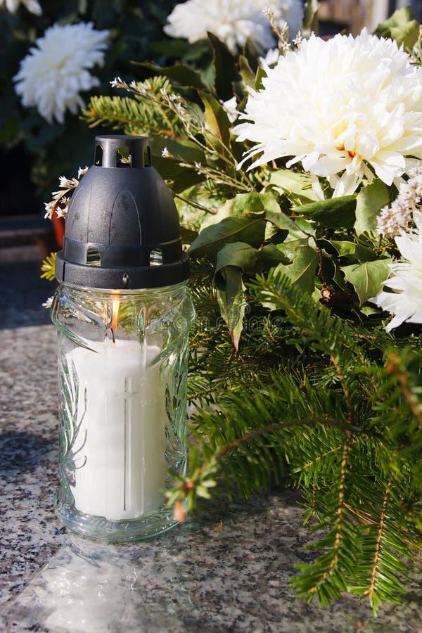 Vela blanca y flores artificiales en un sepulcro imagen de archivo libre de regalías