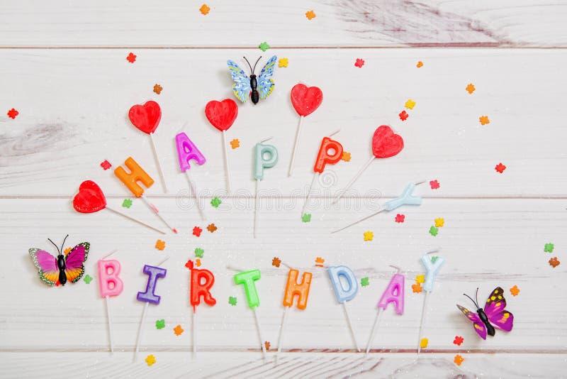 Vela, borboleta e confetes no fundo de madeira Aniversário ho imagens de stock royalty free