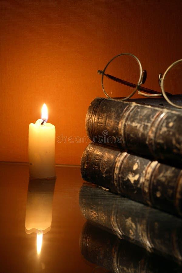 Vela da iluminação perto do livro fotos de stock royalty free