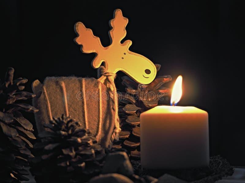 Vela de la Navidad que quema con los alces de los conos de madera y del pino fotos de archivo