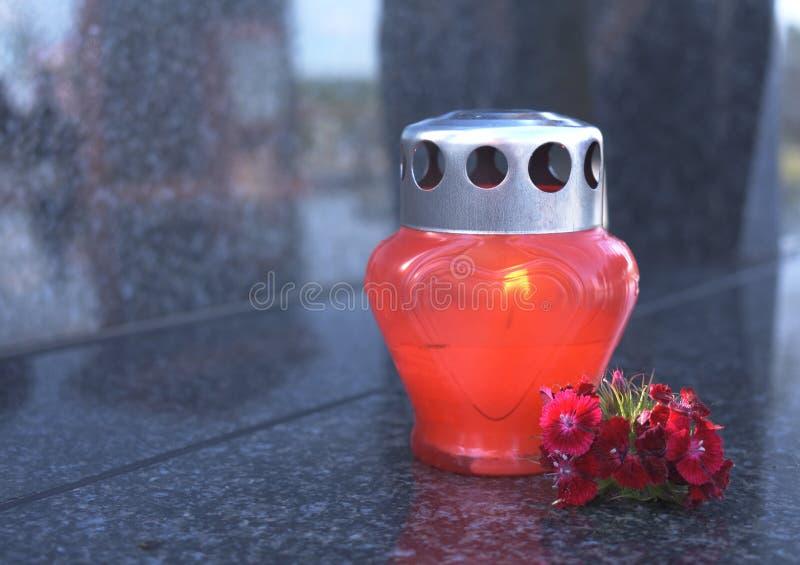 Vela de luto y flores rojas en la piedra sepulcral imagen de archivo libre de regalías