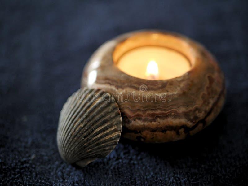 Vela de pedra da luz do chá com mar Shell na obscuridade da marinha - azul imagem de stock