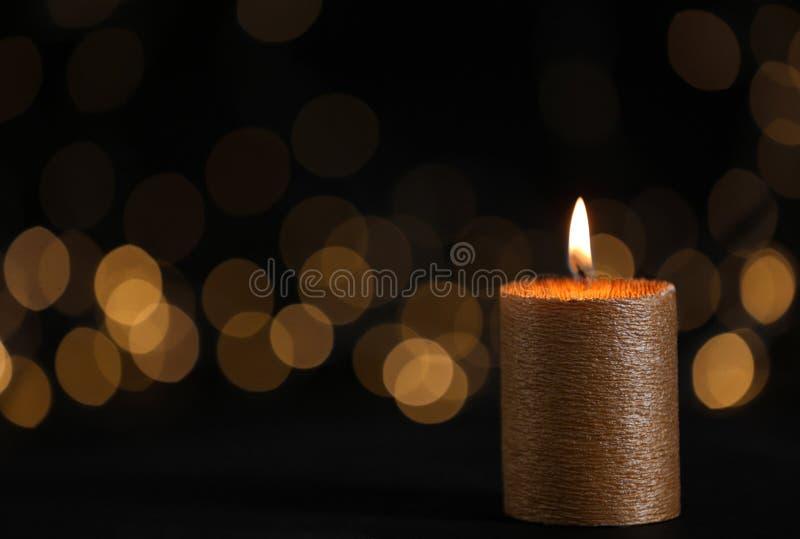 Vela de queimadura do ouro contra luzes borradas na escurid?o foto de stock royalty free