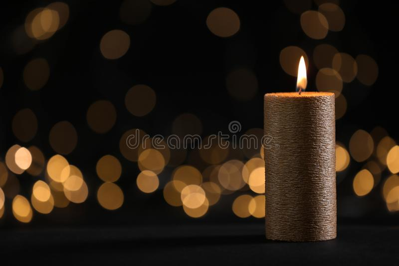 Vela de queimadura do ouro contra luzes borradas na escurid?o foto de stock