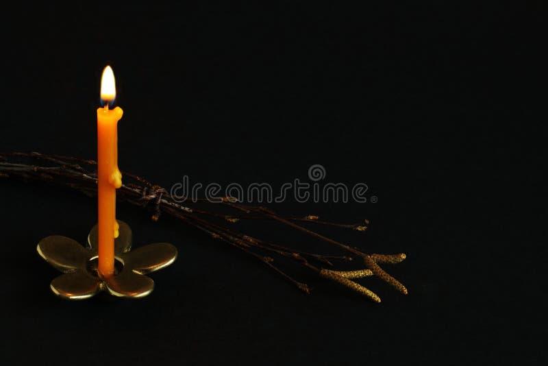 Vela de queimadura no castiçal de bronze no formulário da flor e no ramo do vidoeiro com brincos em um fundo preto Conceito easte imagens de stock