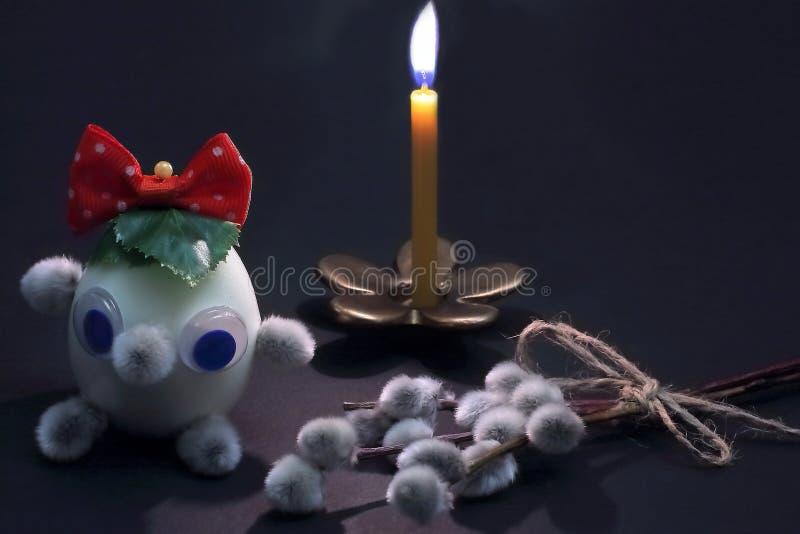 Vela de queimadura no castiçal de bronze na forma da flor e do caráter inventado da Páscoa do tipo feitos do ovo e dos botões fotografia de stock royalty free