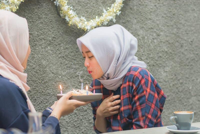 Vela de sopro da mulher atrativa do hijab de seu bolo de aniversário foto de stock