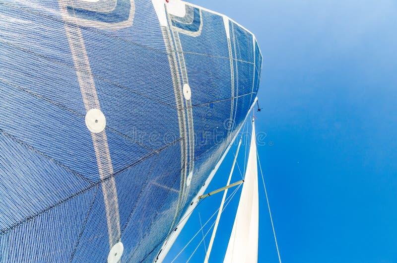 Vela de un barco de navegación del catamarán contra el cielo azul claro fotos de archivo