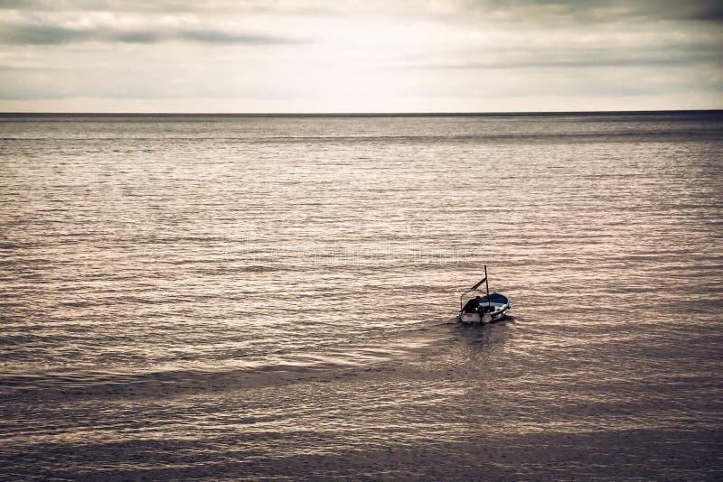 Vela del barco de navegación lejos en el mar hacia horizonte durante puesta del sol con el espacio de la copia en los colores ent fotografía de archivo
