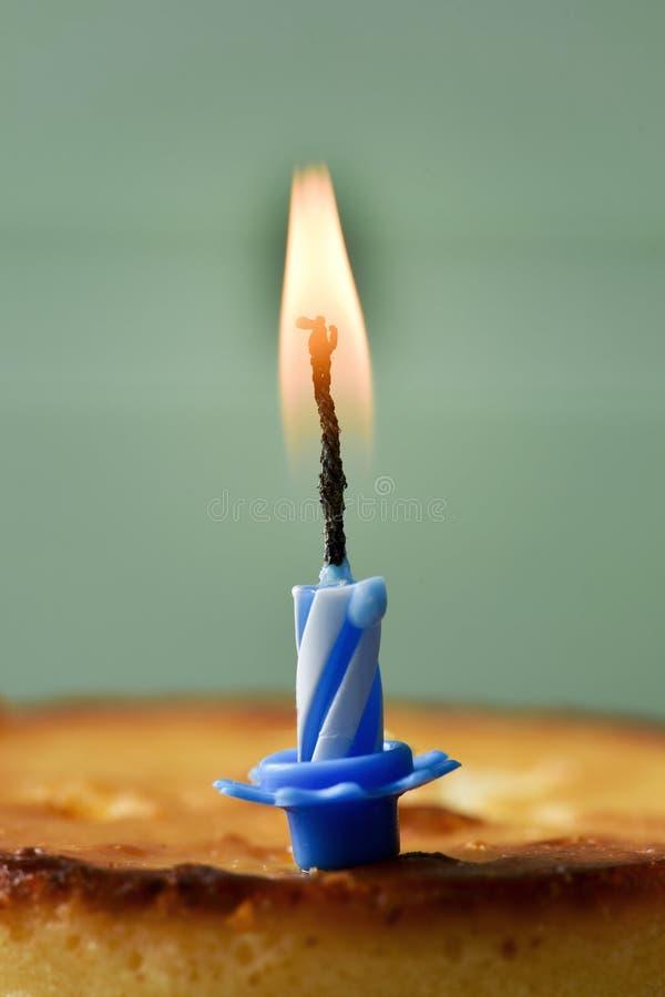 Vela del cumpleaños del Lit en un pastel de queso fotos de archivo