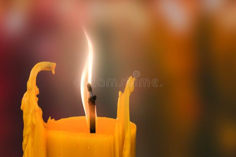 Vela delante de muchos candleflames defocused que crean un alcohol fotos de archivo