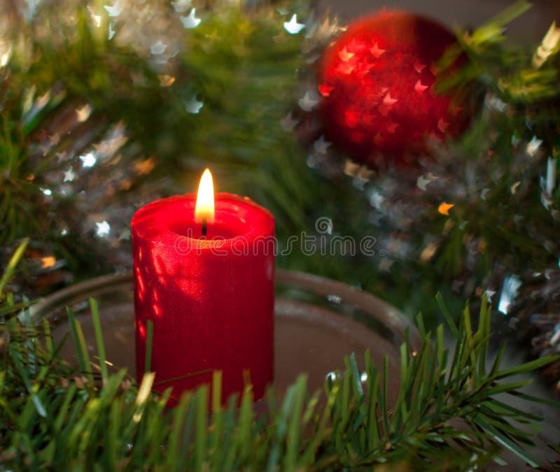 Vela do Natal com uma grinalda e um ornamento vermelho foto de stock royalty free