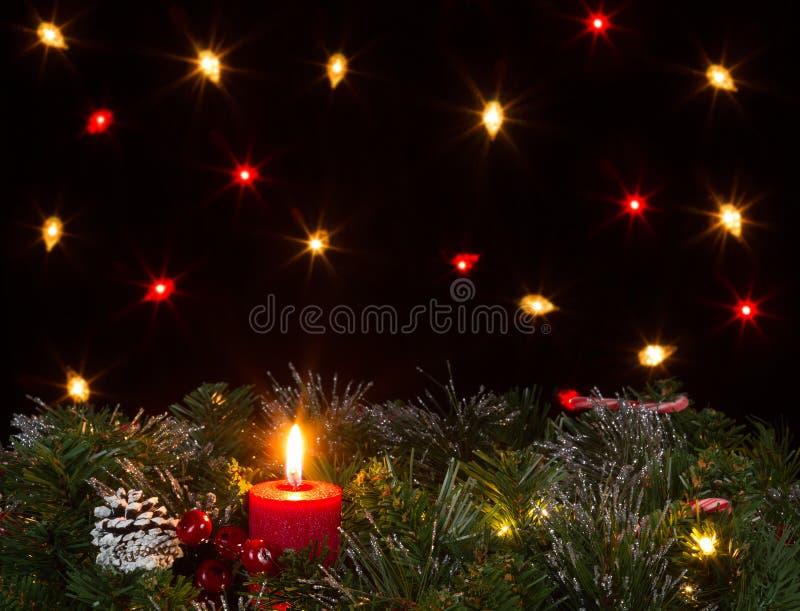 Vela do Natal que queima-se com fundo sempre-verde e escuro com imagens de stock royalty free