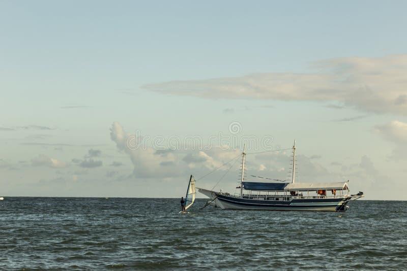 Vela do windsurfe pelo mar no por do sol perto de um barco com palma foto de stock royalty free
