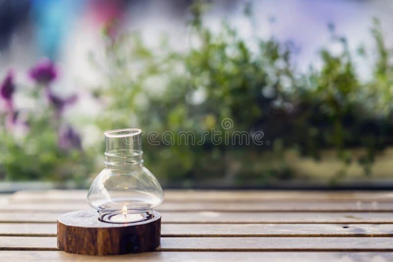 Vela en una palmatoria en una tabla de madera y flores violetas de la calle detrás, espacio de la copia imagen de archivo