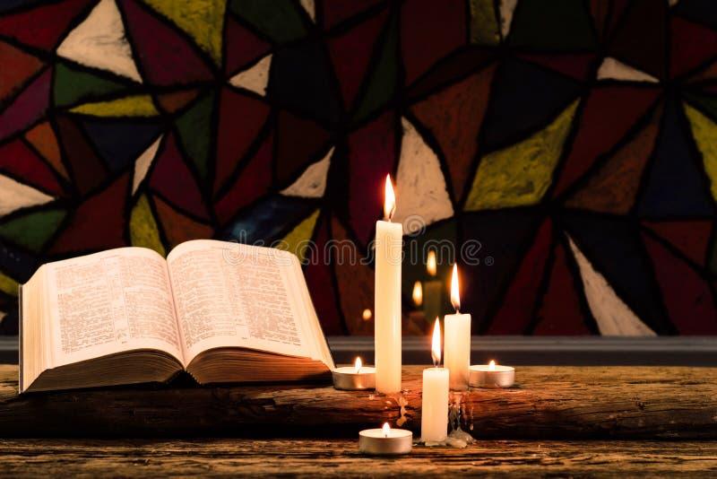 Vela en una tabla de madera del roble viejo Fondo hermoso de los vitrales Concepto de la religión foto de archivo libre de regalías