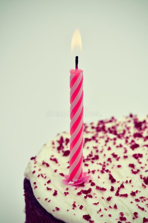 Vela encendida en una torta, vignetted fotos de archivo