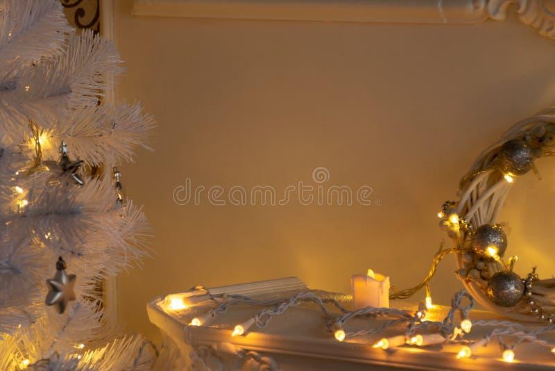 Vela, guirnalda, guirnalda en un estante de la chimenea y puntillas del árbol de navidad blanco teniendo en cuenta luces fotos de archivo libres de regalías