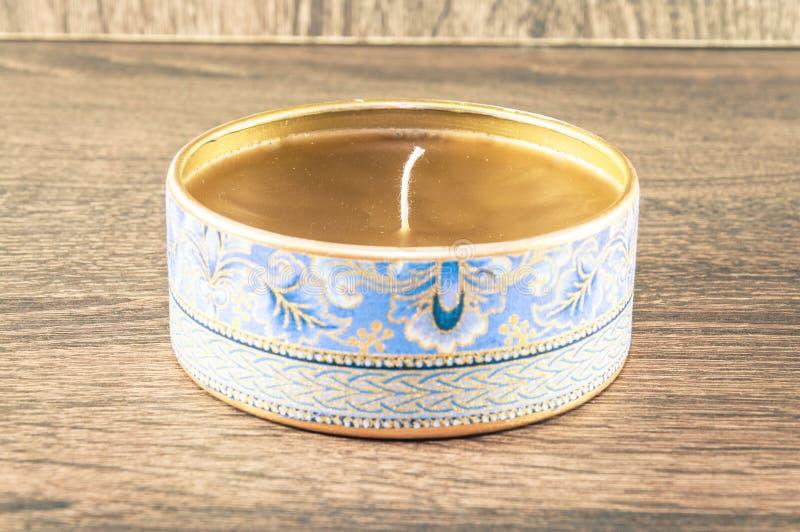 Vela hecha a mano hecha en la caja redondeada de oro adornada con la tela texturizada imagen de archivo