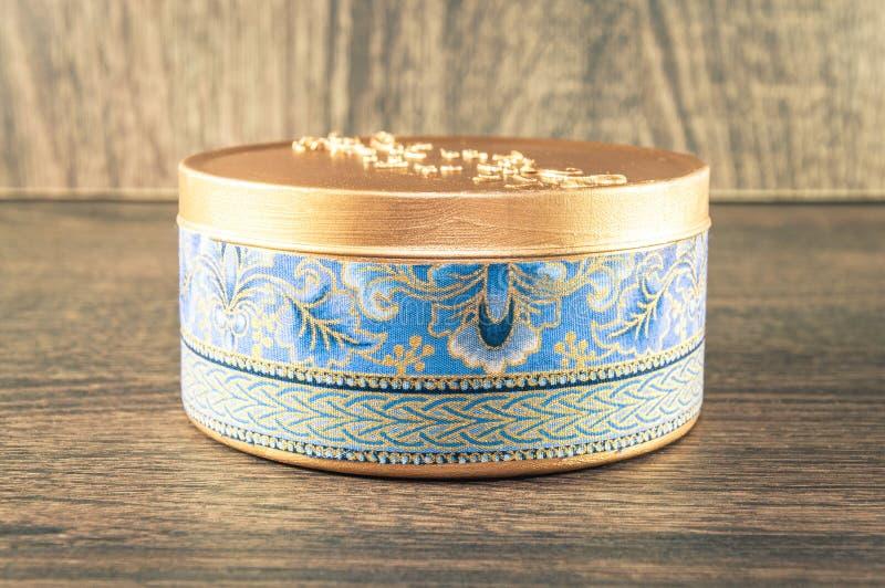 Vela hecha a mano hecha en la caja redondeada de oro adornada con la tela texturizada imagen de archivo libre de regalías