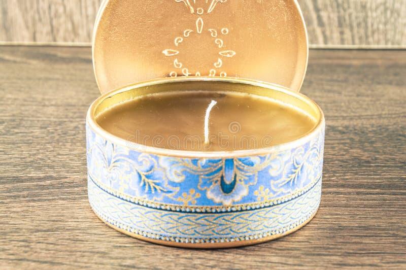 Vela hecha a mano hecha en la caja redondeada de oro adornada con la tela texturizada foto de archivo libre de regalías