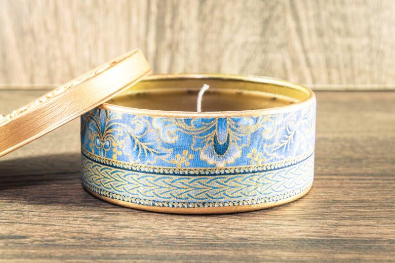 Vela hecha a mano hecha en la caja redondeada de oro adornada con la tela texturizada imágenes de archivo libres de regalías