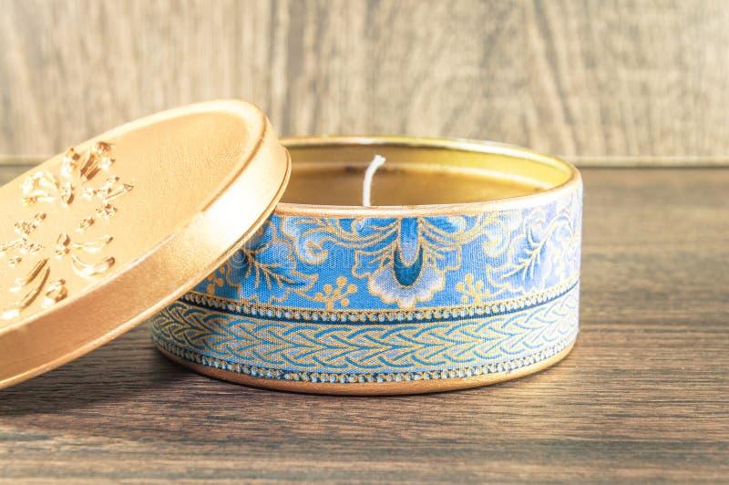 Vela hecha a mano hecha en la caja redondeada de oro adornada con la tela texturizada fotos de archivo