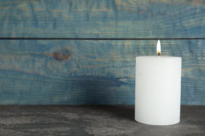 Vela illuminada de la cera en la tabla fotografía de archivo libre de regalías