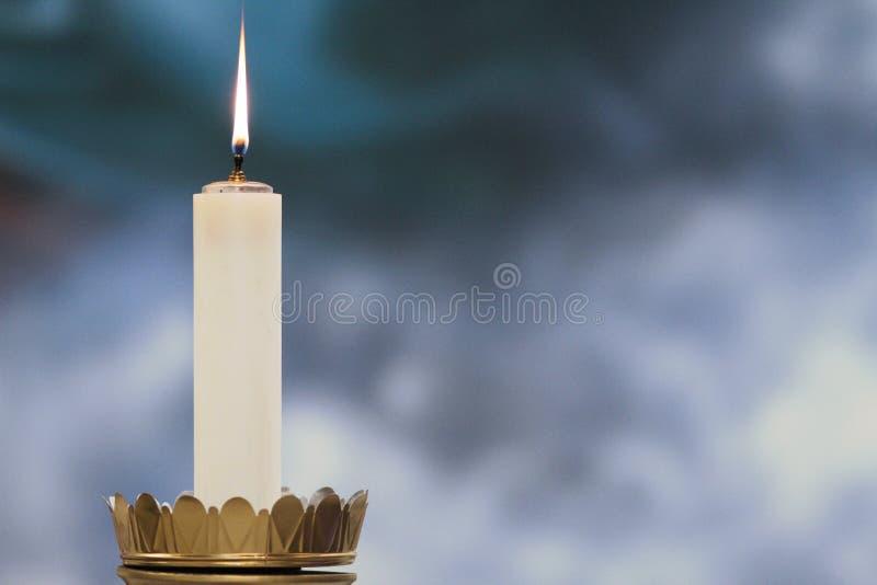 Vela iluminada durante uma massa católica fotografia de stock