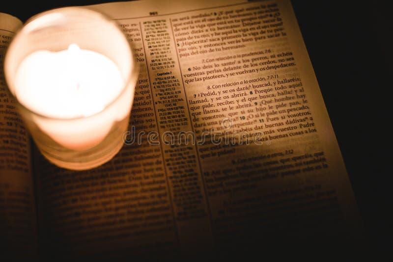 Vela iluminada en un tarro en un libro de la biblia escrito en español en un cuarto oscuro foto de archivo libre de regalías