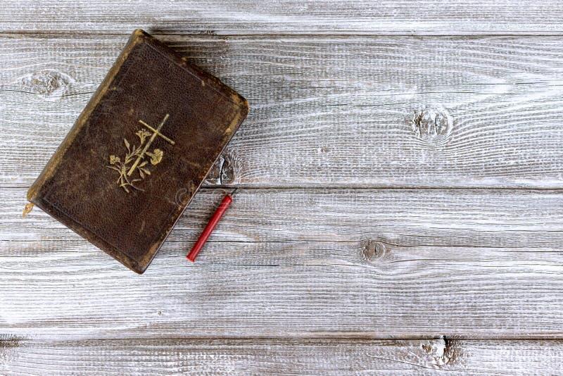 Vela inflamable de la biblia católica y de la iglesia roja en fondo de madera con el espacio de la copia fotografía de archivo