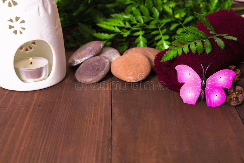 Vela na lâmpada, nas pedras e na toalha do aroma decoradas com samambaia e p fotos de stock royalty free