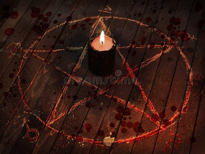 Vela negra asustadiza en círculo del pentagram con descensos sangrientos imagen de archivo