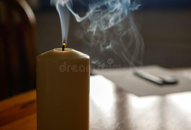 Vela que fuma en la tabla de madera después de descargar la llama imágenes de archivo libres de regalías