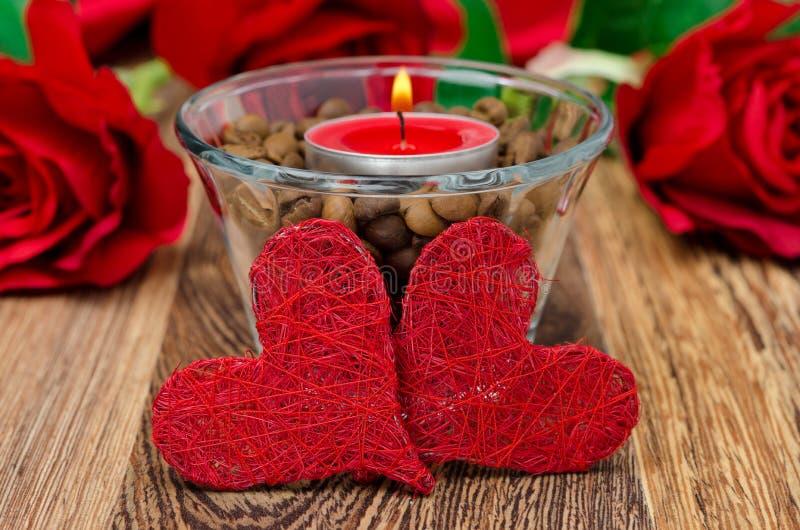 Vela roja en una taza de cristal con los granos de café y dos corazones foto de archivo