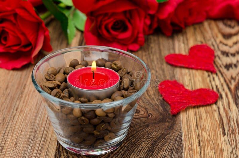Vela roja en una taza de cristal con los granos, las rosas y los corazones de café foto de archivo libre de regalías