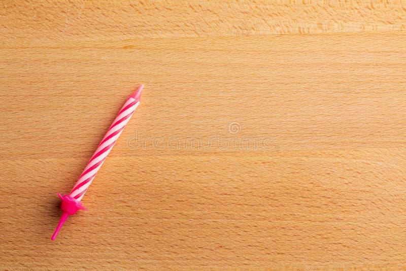 1 vela rosada del cumpleaños en fondo de madera Para la tarjeta de felicitación del cumpleaños Espacio para insertar el texto imagen de archivo libre de regalías