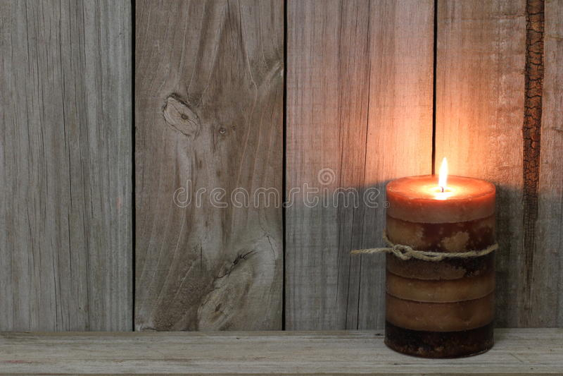 Vela texturizada encendida contra el fondo de madera imágenes de archivo libres de regalías