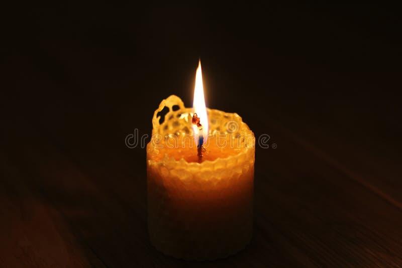 Vela, una llama de vela en el primer de la noche en un fondo negro fotos de archivo