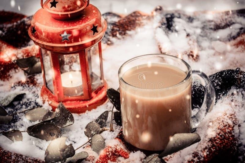 Vela vermelha festiva na lanterna e na caneca de café no tapete com neve imagem de stock